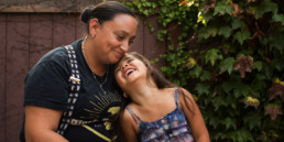 Susanna and daughter laugh together in front of their home.